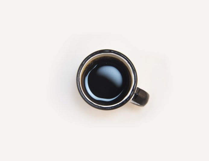 cup of black coffee on a white table