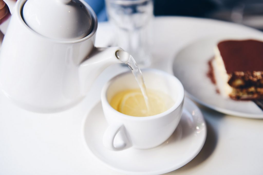 hot water pouring from a teapot into a white mug with a lemon slice