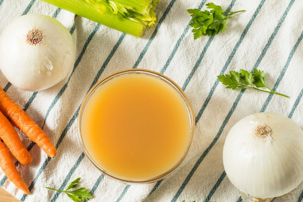 chicken broth in a cup on a table cloth with onions and carrots